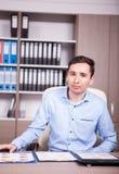 Νέος επιχειρηματίας στο γραφείο που εξετάζει τα διαγράμματα Στοκ Εικόνα