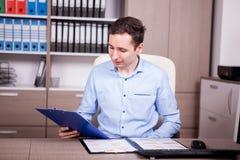 Νέος επιχειρηματίας στο γραφείο που εξετάζει τα διαγράμματα Στοκ φωτογραφία με δικαίωμα ελεύθερης χρήσης