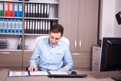 Νέος επιχειρηματίας στο γραφείο που εξετάζει τα διαγράμματα Στοκ Εικόνες