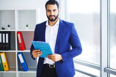 Νέος επιχειρηματίας στο γραφείο που λειτουργεί στον υπολογιστή Στοκ Εικόνες