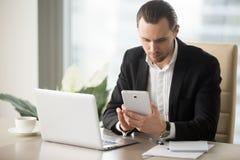 Νέος επιχειρηματίας στο γραφείο που ψάχνει τις πληροφορίες για το electroni Στοκ Φωτογραφία