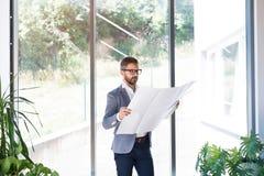 Νέος επιχειρηματίας στο γραφείο του που μελετά τα σχέδια Στοκ Εικόνες
