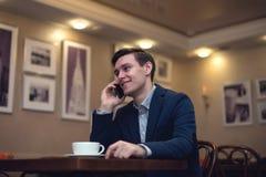 Νέος επιχειρηματίας στο τηλέφωνο με ένα χαμόγελο δικοί του Στοκ Εικόνες