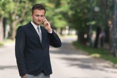 Νέος επιχειρηματίας στο τηλέφωνο υπαίθρια στο πάρκο Στοκ Εικόνες