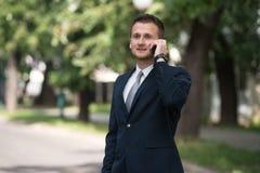 Νέος επιχειρηματίας στο τηλέφωνο υπαίθρια στο πάρκο Στοκ Εικόνα