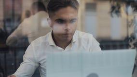 Νέος επιχειρηματίας χρησιμοποιώντας το φορητό προσωπικό υπολογιστή στην άνετη καφετερία και πίνοντας τον καφέ απόθεμα βίντεο
