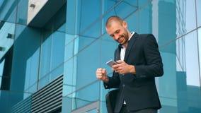 Νέος επιχειρηματίας χρησιμοποιώντας το smartphone κοντά στο γραφείο και γιορτάζοντας το επίτευγμα Το επιχειρησιακό άτομο ανακάλυψ απόθεμα βίντεο