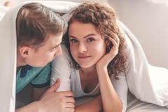 Νέος εραστής καυκάσιος έχοντας έναν γλυκό χρόνο μαζί κάτω από το άσπρο κάλυμμα κατά μήκος του Σαββατοκύριακου Γυναίκες που εξετάζ στοκ φωτογραφία με δικαίωμα ελεύθερης χρήσης