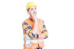 Νέος εργάτης οικοδομών ή μηχανικός που σκέφτεται και που κοιτάζει μακριά Στοκ φωτογραφία με δικαίωμα ελεύθερης χρήσης