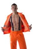 Νέος εργάτης οικοδομών με το πορτοκαλί κοστούμι ανοικτό στο γυμνό κορμό Στοκ Εικόνες