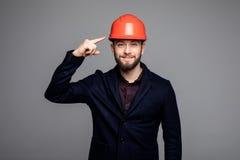 Νέος εργάτης οικοδομών που δείχνεται στο σκληρό καπέλο Στοκ Φωτογραφίες