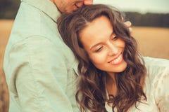 Νέος ερωτευμένος υπαίθριος ζευγών αγκάλιασμα ζευγών Νέα όμορφη ερωτευμένη παραμονή ζευγών και φίλημα στον τομέα στο ηλιοβασίλεμα Στοκ Φωτογραφίες