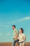 Νέος ερωτευμένος υπαίθριος ζευγών Τρεξίματα ζεύγους πέρα από τον τομέα Στοκ Φωτογραφίες