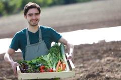 Νέος ευτυχής αγρότης με ένα σύνολο κλουβιών του λαχανικού Στοκ Εικόνες