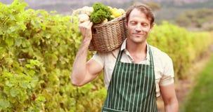 Νέος ευτυχής αγρότης που κρατά ένα καλάθι των λαχανικών φιλμ μικρού μήκους