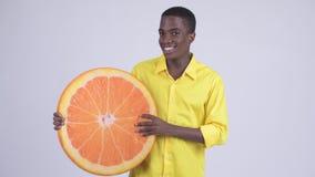 Νέος ευτυχής αφρικανικός επιχειρηματίας που δαγκώνει το πορτοκαλί μαξιλάρι ως υγιή έννοια απόθεμα βίντεο
