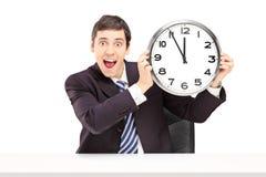 Νέος ευτυχής επιχειρηματίας που κρατά ένα ρολόι Στοκ φωτογραφία με δικαίωμα ελεύθερης χρήσης