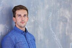 Νέος ευτυχής επιχειρηματίας στο γκρίζο υπόβαθρο Στοκ φωτογραφία με δικαίωμα ελεύθερης χρήσης