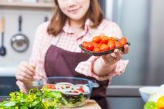 Νέος ευτυχής θηλυκός μάγειρας που αντέχει μια συσκευασία των κόκκινων ντοματών Στοκ φωτογραφίες με δικαίωμα ελεύθερης χρήσης
