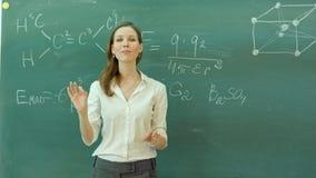Νέος ευτυχής θηλυκός δάσκαλος με τα όπλα που διασχίζονται στάση ενάντια στον πράσινο πίνακα απόθεμα βίντεο