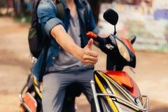 Νέος ευτυχής και όμορφος αρσενικός μοτοσυκλετιστής που οδηγά στη μοτοσικλέτα που δίνει τους αντίχειρες επάνω και το θετικό Στοκ Εικόνες