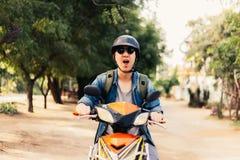 Νέος ευτυχής και όμορφος αρσενικός μοτοσυκλετιστής στα γυαλιά ηλίου και κράνος που οδηγά στη μοτοσικλέτα Στοκ Εικόνες