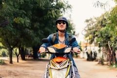 Νέος ευτυχής και όμορφος αρσενικός μοτοσυκλετιστής στα γυαλιά ηλίου και κράνος που οδηγά στη μοτοσικλέτα Στοκ φωτογραφία με δικαίωμα ελεύθερης χρήσης