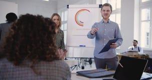 Νέος ευτυχής καυκάσιος επιχειρηματίας που οδηγεί τη multiethnic ομάδα στον κύκλο μαθημάτων κατάρτισης πωλήσεων ομάδων γραφείων Υγ απόθεμα βίντεο