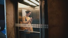 Νέος ευτυχής οδηγώντας ανελκυστήρας γυναικών χαμόγελου με το διαφανή τοίχο γυαλιού, που περπατά έξω χρησιμοποιώντας τις αγορές ap απόθεμα βίντεο