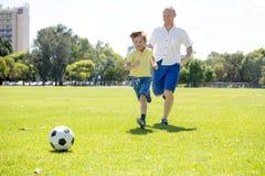 Νέος ευτυχής πατέρας και συγκινημένος λίγα χρονών γιος 7 ή 8 που παίζει μαζί το ποδόσφαιρο ποδοσφαίρου στον κήπο πάρκων πόλεων πο στοκ εικόνες