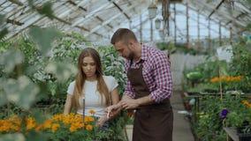 Νέος εύθυμος ανθοκόμος ατόμων που μιλά στον πελάτη και που δίνει τις συμβουλές εργαζόμενος στο κέντρο κήπων απόθεμα βίντεο