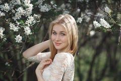 Νέος εύθυμος ξανθός κήπος μήλων ανθών απόλαυσης Ανθίζοντας ελατήριο, αγάπη, έννοια ευτυχίας Στοκ Φωτογραφία