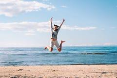 Νέος εύθυμος πηδώντας ενθουσιασμός έφηβη στην παραλία στοκ εικόνα