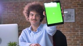 Νέος εύθυμος nerdy επιχειρηματίας που παρουσιάζει ταμπλέτα με το κλειδί χρώματος στη κάμερα και το χαμόγελο, που κάθονται στο σύγ φιλμ μικρού μήκους