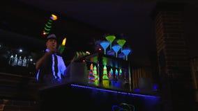 Νέος, ελκυστικός επαγγελματικός μπάρμαν, bartender που κάνει τα δροσερά, επαγγελματικά, καταπληκτικά τεχνάσματα με δύο μπουκάλια, απόθεμα βίντεο