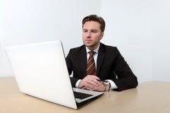 Νέος ελκυστικός επιχειρηματίας που εξετάζει τον υπολογιστή Στοκ Φωτογραφία