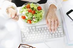 Νέος δημιουργικός σχεδιαστής γυναικών που τρώει μια σαλάτα εργαζόμενος στην αρχή. Στοκ Εικόνες