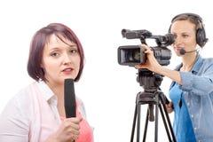 Νέος δημοσιογράφος γυναικών με ένα μικρόφωνο και camerawoman Στοκ εικόνες με δικαίωμα ελεύθερης χρήσης