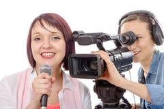 Νέος δημοσιογράφος γυναικών με ένα μικρόφωνο και camerawoman Στοκ φωτογραφία με δικαίωμα ελεύθερης χρήσης
