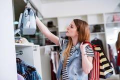 Νέος θηλυκός αγοραστής με τις τσάντες αγορών που επιλέγει την τσάντα που ταιριάζει με το περιστασιακό ύφος της Στοκ εικόνα με δικαίωμα ελεύθερης χρήσης