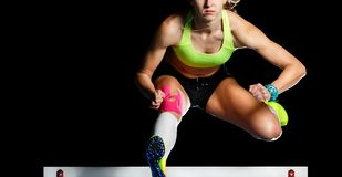 Νέος θηλυκός αθλητής που πηδά πέρα από το εμπόδιο στην ορμή στοκ εικόνα