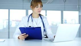 Νέος θηλυκός γιατρός που διαβάζει τις ιατρικές εκθέσεις και που εργάζεται στο lap-top στοκ φωτογραφίες με δικαίωμα ελεύθερης χρήσης