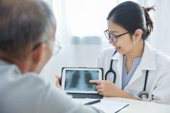 Νέος θηλυκός γιατρός που συζητά με τον ανώτερο ασθενή ατόμων Στοκ εικόνα με δικαίωμα ελεύθερης χρήσης