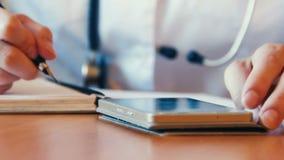 Νέος θηλυκός γιατρός που χρησιμοποιεί το σύγχρονο smartphone στο νοσοκομείο, που αναζητά τις πληροφορίες στο Διαδίκτυο Κλείστε επ απόθεμα βίντεο