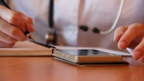 Νέος θηλυκός γιατρός που χρησιμοποιεί το σύγχρονο smartphone απόθεμα βίντεο
