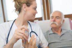 Νέος θηλυκός γιατρός που χρησιμοποιεί το lancelet στο ανώτερο αρσενικό δάχτυλο ασθενών στοκ εικόνες