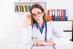 Νέος θηλυκός γιατρός σε ομοιόμορφο στο ofice γιατρών ` s που γράφει ένα έγγραφο στοκ εικόνα