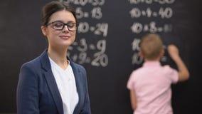 Νέος θηλυκός δάσκαλος που κοιτάζει στη κάμερα, μαθητής που λύνει math τις ασκήσεις, εργασία φιλμ μικρού μήκους