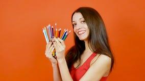 Νέος θηλυκός δημιουργικός σχεδιαστής με τα ζωηρόχρωμα μολύβια που θέτουν σε ένα πορτοκαλί υπόβαθρο έννοια σχεδίου τέχνης φιλμ μικρού μήκους