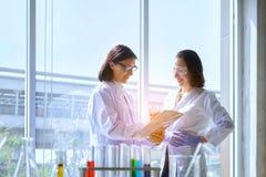 Νέος θηλυκός επιστήμονας που στέκεται με το techer στην παραγωγή εργαζομένων εργαστηρίων στοκ εικόνα